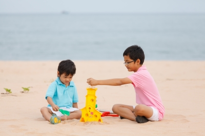 Siblings playing in the sand on the beach.